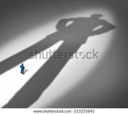 Under a shadow business metaphor for living under a powerful leader or small business competing against giants as a businessman facing a huge darkness shaped as a giant man. - stock photo