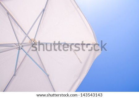 Under a white beach umbrella looking up into the opened parasol with its metal spokes against a blue sunny sky - stock photo