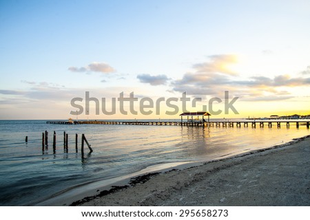 Under clear skies a distant jetty is lined with golden light of a setting sun over quiet waters in San Pedro in Ambergris Caye in Belize South America - stock photo