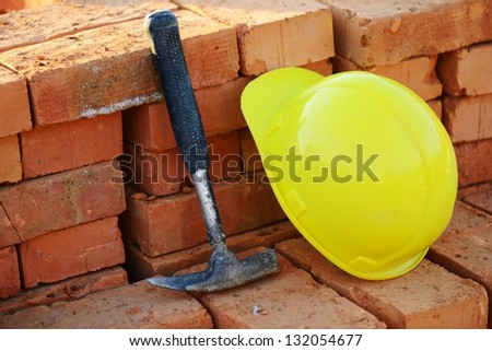 Under construction, helmet with hammer and bricks for building site - stock photo