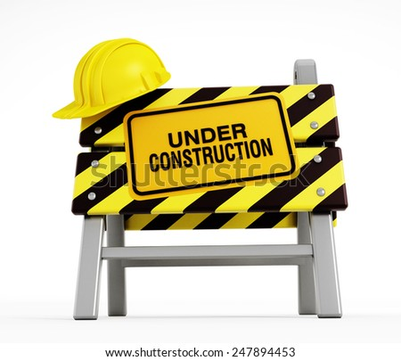 Under construction sign and hardhat on construction barrier - stock photo