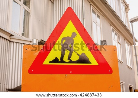 Under construction sign in a street with buildings - stock photo