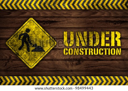under construction sign on wooden background - stock photo