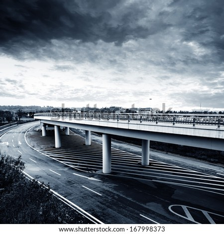 Under overcast skies, modern city viaduct. - stock photo