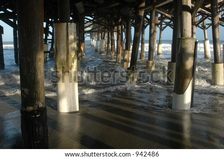 Under pier with incoming tide - stock photo