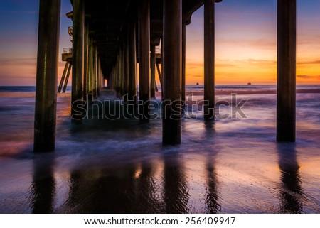 Under the pier at sunset, in Huntington Beach, California. - stock photo