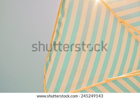 Under the sunshade with view of blue sky and Sun reflections - stock photo