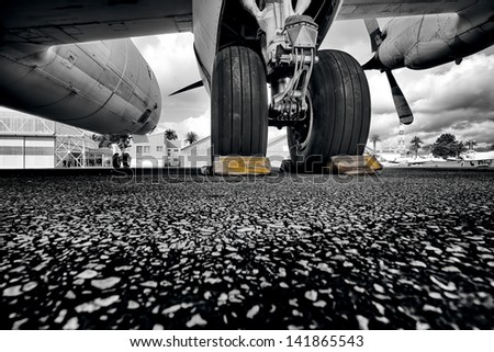 under the wing of plane, black and white - stock photo