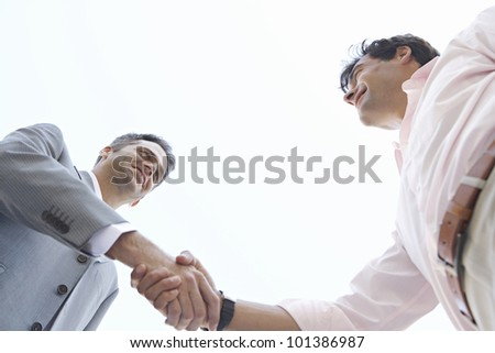 Under view of two businessmen shaking hands, with the sky behind them. - stock photo