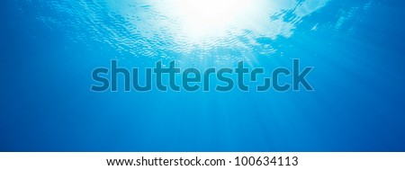 under water, abstract panorama of sun rays in the ocean - stock photo