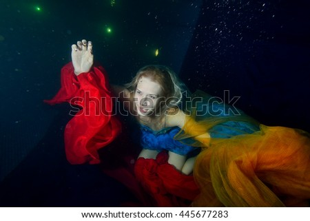 Under water beautiful girl emerges from the depths to the surface of the water. Tends up with red and orange cloth. Portrait. The view from the top. Horizontal orientation. - stock photo