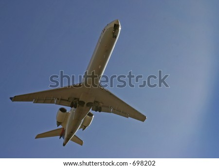 Underbelly of a jet airplane coming in for a landing - stock photo