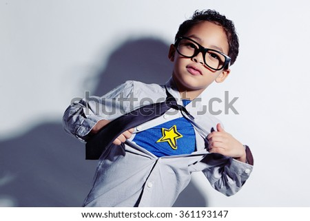 Undercover.  Adorable mixed race boy ripping off his dress shirt to uncover his superhero costume underneath.   - stock photo