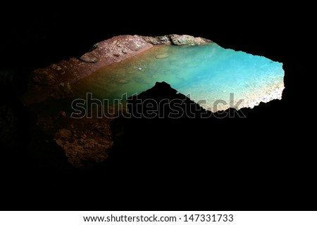 Underground lake viewed from a cave - stock photo