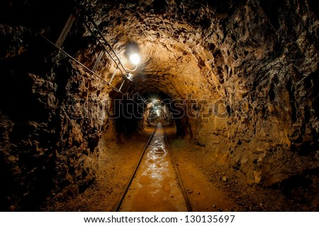 Underground mine passage with rails and light - stock photo