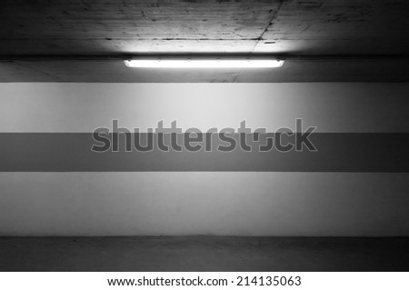 Underground parking wall and a lamp - stock photo