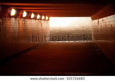 Underground passage with lights and stairs in glowing end - stock photo