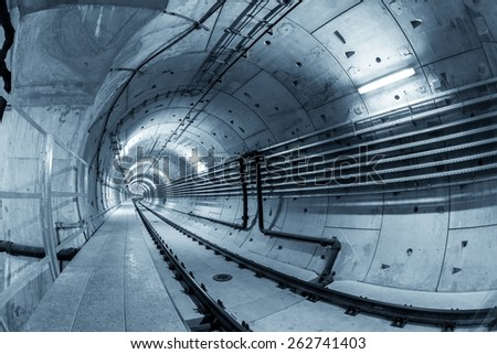 Underground tunnel for the subway leading deep down - stock photo