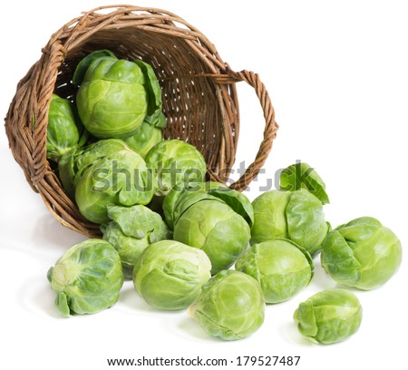 underlying basket with brussel sprouts  spilling on a white  - stock photo