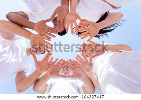 underneath view of happy people hands together outdoors - stock photo