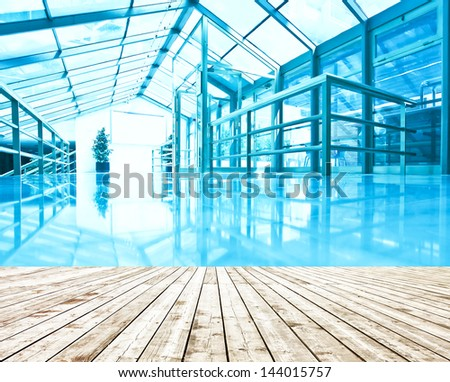 Underside wide angled and perspective view to steel blue glass airport ceiling through high rise building skyscrapers, business concept of successful industrial architecture  with wooden planks floor - stock photo