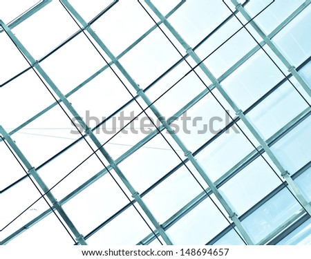 underside wide angled and perspective view to steel blue glass airport ceiling through high rise building skyscrapers, business concept of successful industrial architecture - stock photo