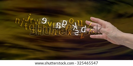 Understanding Dyslexia Website Banner -  female hand with the alphabet flowing from fingers in gold with six letters flipped in white to symbolize dyslexia  - stock photo