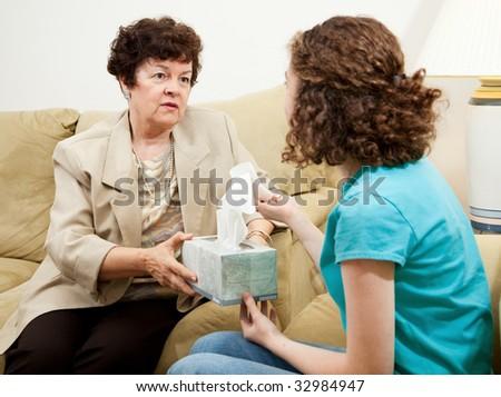 Understanding therapist handing tissue box to an upset teen patient. - stock photo