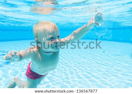 Underwater boy with an empty bottle in his hand - stock photo