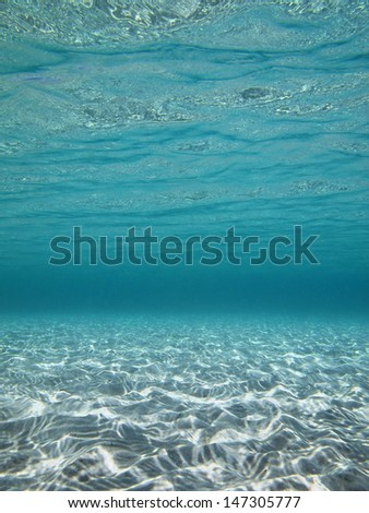 Underwater lights reflected on a sandy sea floor in clear shallow water - stock photo