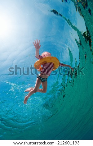 Underwater photo of a little girl swimming with inflatable ring in pool - stock photo