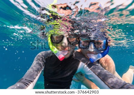 Underwater photo of a young couple snorkeling at tropical ocean - stock photo