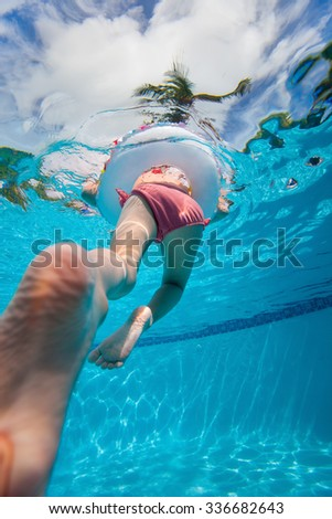 Underwater photo of adorable little girl swimming in pool on summer vacation - stock photo