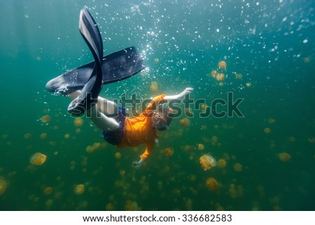 Underwater photo of tourist child snorkeling with endemic stingless jellyfish in lake at Palau. Snorkeling in Jellyfish Lake is a popular activity for tourists to Palau. - stock photo