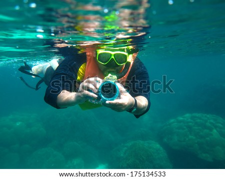 Underwater portrait of a man snorkeling in Andaman Sea with his camera. - stock photo