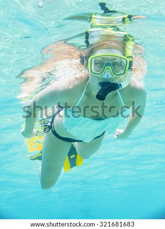 Underwater portrait of a woman snorkeling in clear tropical sea - stock photo