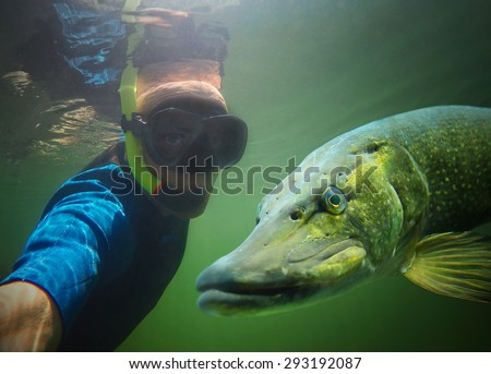 Underwater selfie with friend. Scuba diver and pike in deep lake. - stock photo
