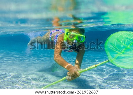 Underwater shoot of a cute girl snorkeling with scoop-net in a tropical sea - stock photo