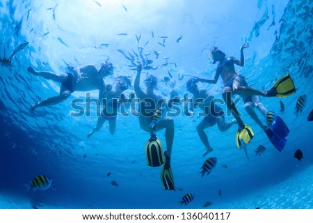 Underwater shoot of a group of friends snorkeling in a clear sea and feeding fish - stock photo