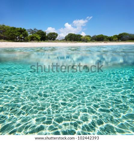 Underwater shoot of a sandy sea bottom and wild tropical island's coastline - stock photo