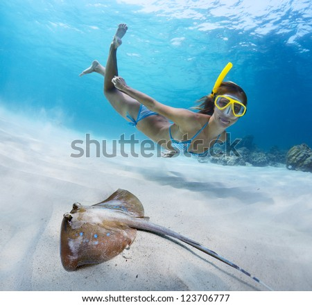 Underwater shoot of a young lady snorkeling and doing skin diving over sandy sea bottom with blue spotted ray on the foreground - stock photo