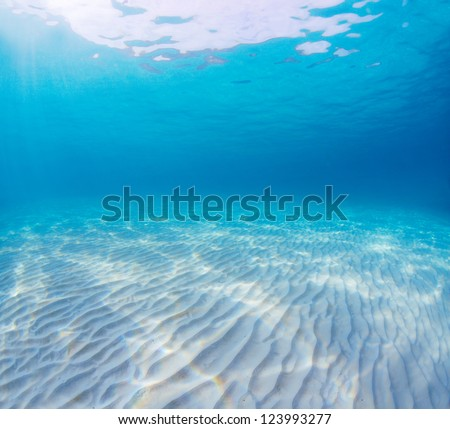 Underwater shoot of an infinite sandy sea bottom with clear blue water and waves on its surface - stock photo