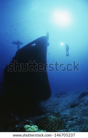 Underwater shoot of female scuba diver exploring sunken ship - stock photo