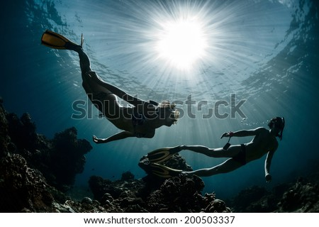 Underwater shot of the couple moving on depth over coral reef - stock photo
