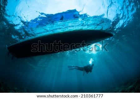 Underwater sunshine below the boat in Gorontalo, Indonesia. There's a boat at surface, so the sun shine through the boat. - stock photo