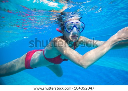 Underwater swimming: young woman swimming underwater in a pool, wearing a diving mask - stock photo