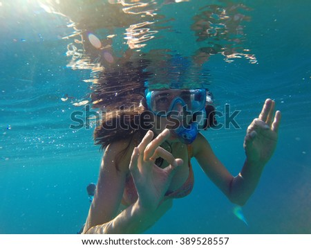 Underwater view of a woman snorkeling in the tropical sea - stock photo
