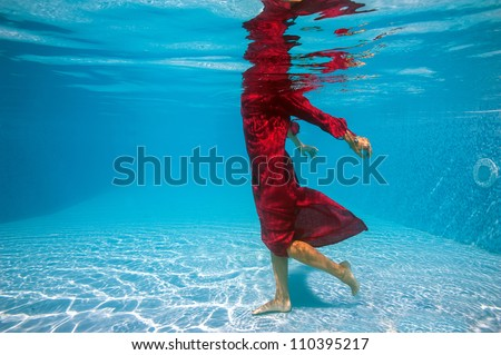 Underwater woman fashion portrait with red dress in swimming pool. - stock photo
