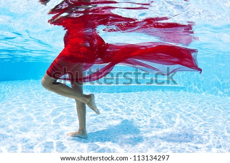 Underwater woman fashion portrait with red veil in swimming pool. - stock photo