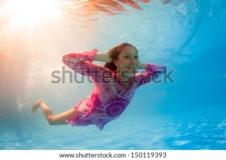 Underwater woman portrait wearing pink dress in swimming pool. - stock photo